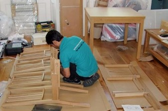 Worker assembling a set of chairs
